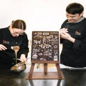 """Nous sommes fiers de vous présenter notre fresque 120 ans entièrement chocolatée ! De la réalisation du chevalet aux pictogrammes, nos maîtres chocolatiers, Emilie et Laurent ont délicieusement interprété en chocolat la fresque """"On l'Adore"""", réalisée par Serge Lowrider. L'ensemble de cette œuvre est réalisé à la main dans notre chocolaterie à Fribourg ! Un tout grand MERCI à l'ensemble de nos 150 collaborateurs pour leur investissement et travail quotidien. N'hésite pas à venir admirer ce chef-d'œuvre dans notre boutique à Fribourg ! . Wir sind stolz darauf, euch unser 120 Jahre-Gemälde ganz aus Schokolade zu präsentieren! Von der Gestaltung der Staffelei bis hin zu den Piktogrammen haben unsere Schokoladenmeister Emilie und Laurent das von Serge Lowrider geschaffenes Wandbild """"On l'Adore"""" vollständig aus feiner Schokolade interpretiert. Das ganze Werk wurde in unserer Schokoladenfabrik in Freiburg von Hand gefertigt! Ein grosses DANKESCHÖN an alle unsere 150 Mitarbeiter für ihren Einsatz und ihre tägliche Arbeit. Dieses Meisterwerk ist in unserem Shop in Freiburg zu bewundern! . @danielabistrain #chocolatvillars120ans#chocolat#120ans#savoirfaire#maîtrechocolatier#fribourg#switzerland#swiss#fresquechocolat#art#villarsmoment"""